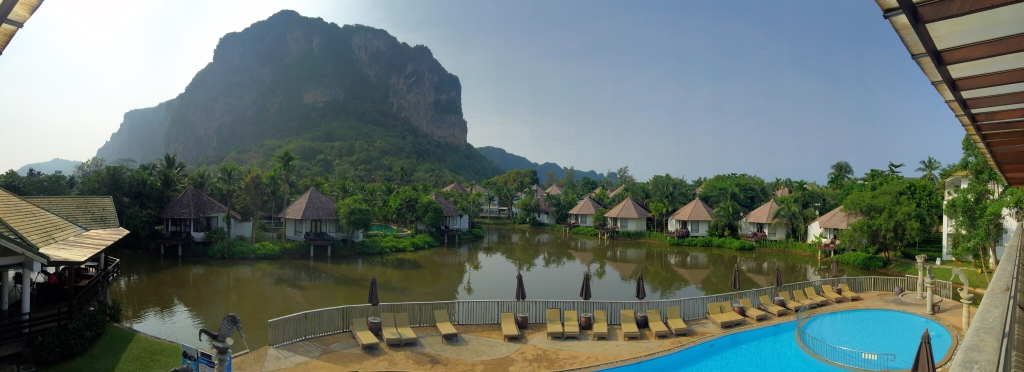 Cottages set around the lagoon, amongst the lush greenery and a majestic view of the limestone cliff